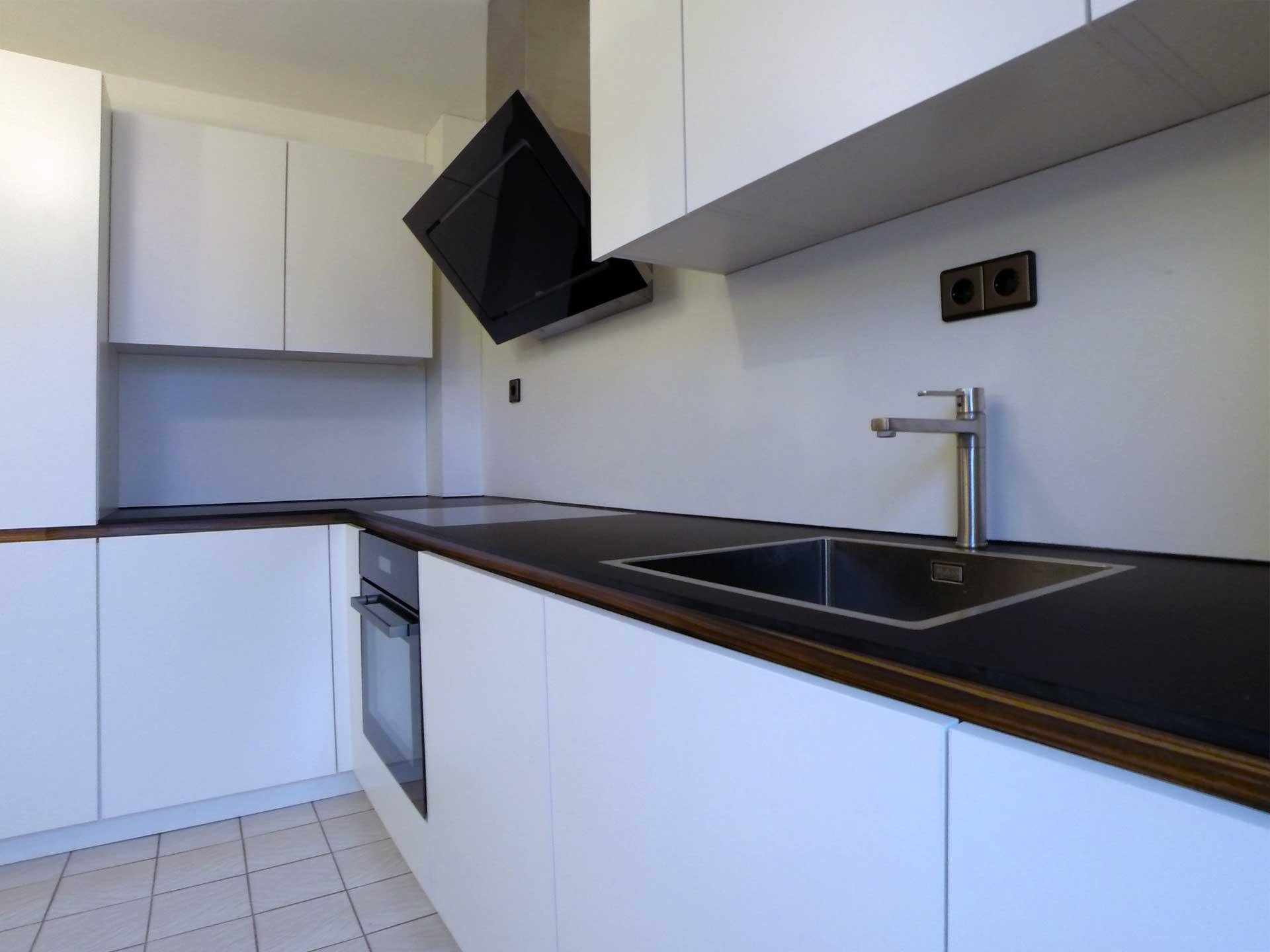 Küche matt weiß griflos mit matt schwarzer Arbeitsplatte und eingelassenem Kochfeld und Spüle