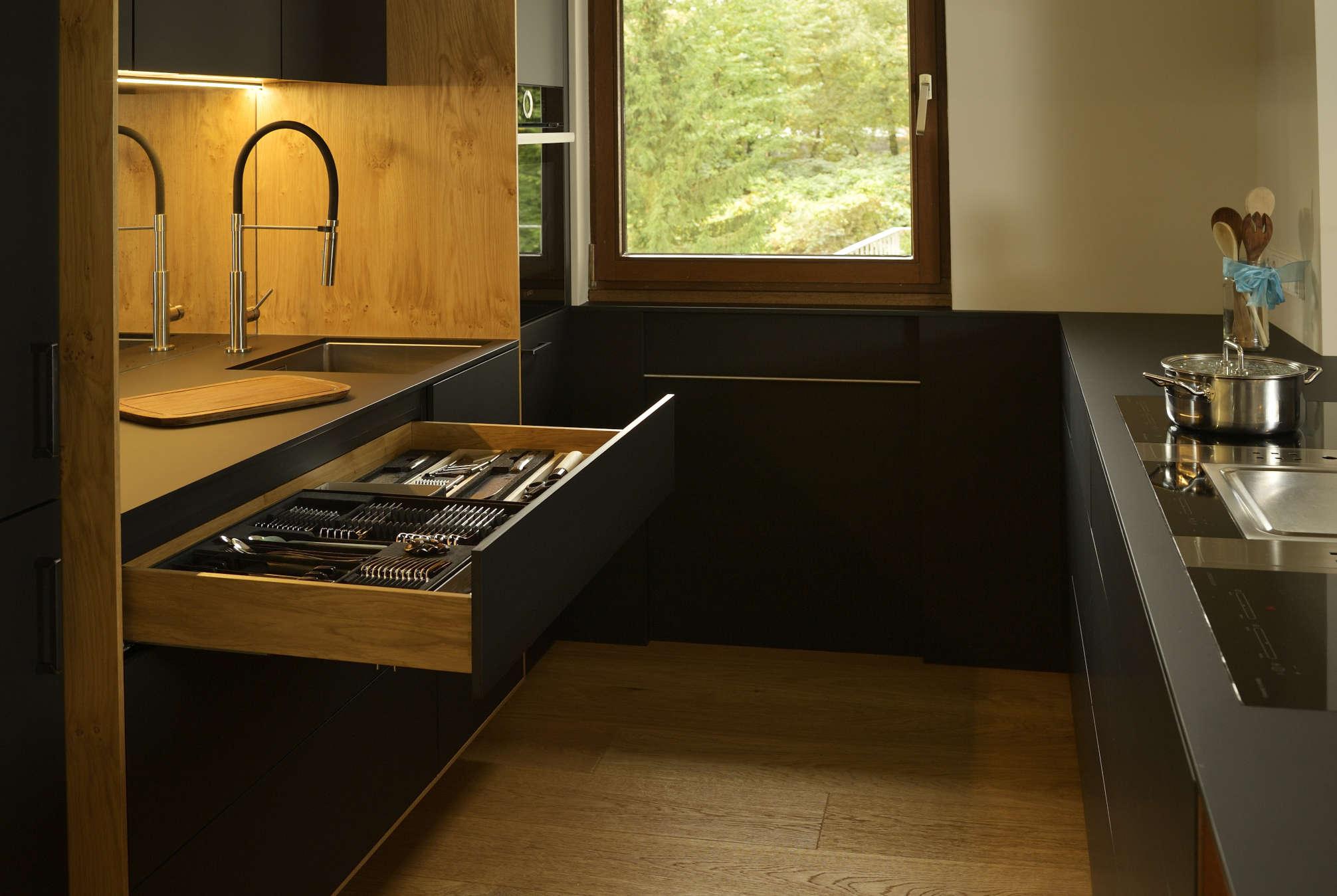 Küche matt schwarz und Holz mit ausgezogener Besteckschublade, eingelassenem Kochfeld und Spüle