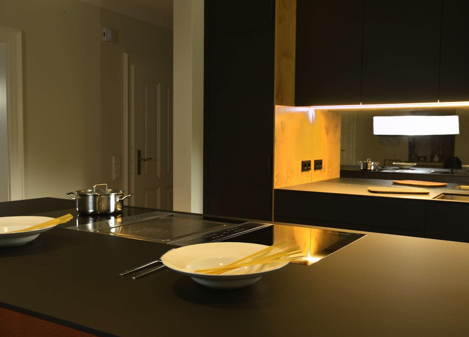 Küche matt schwarz und Holz mit eingelassenem Kochfeld im Mittelteil und weiterem Arbeitsbereich im Hintergrund