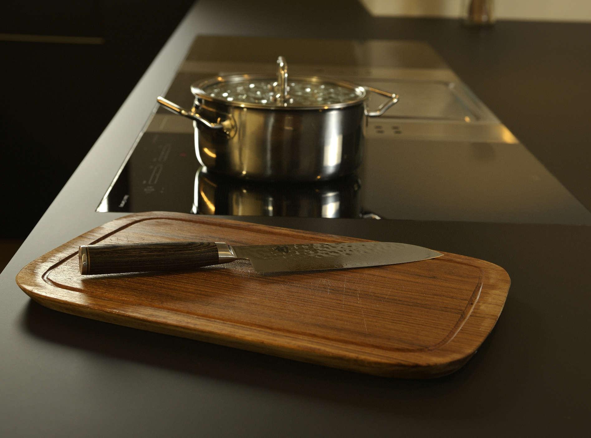 Küche matt schwarz mit eingelassenem Kochfeld, Holzbrett mit Messer auf der Arbeitsplatte