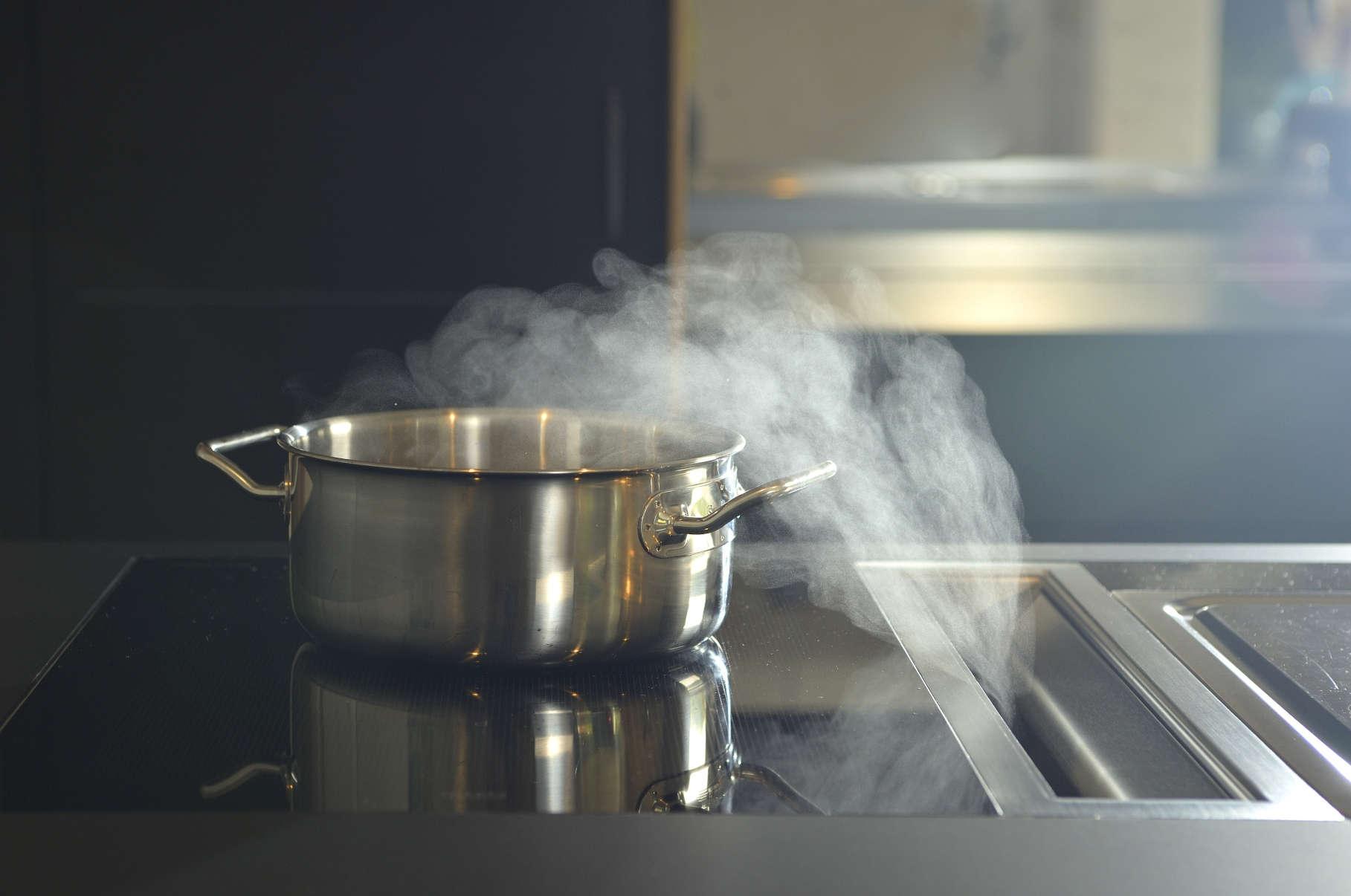 Küche matt schwarz mit eingelassenem Kochfeld und in die Arbeitsplatte integriertem Dunstabzug