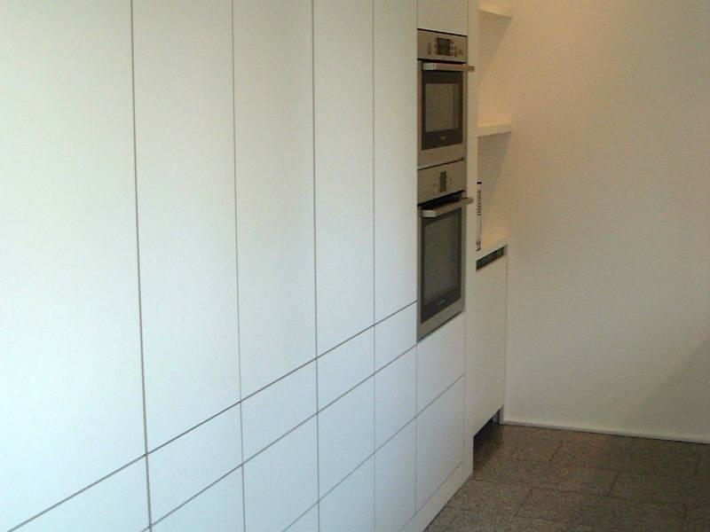 Küche matt weiß grifflos mit hoch eingebautem Backofen und Mikrowelle