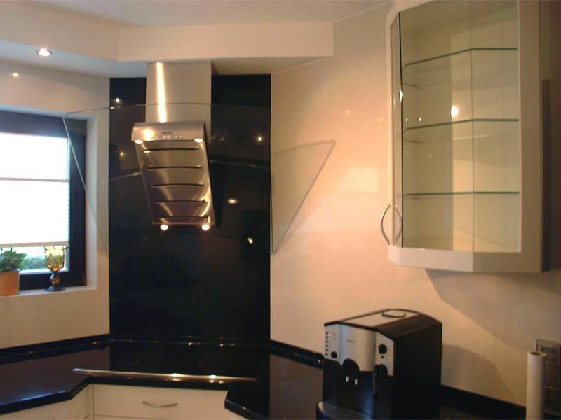 Küche mit Kochfeld und Dunstabzugshaube in der Ecke und Hängeschrank